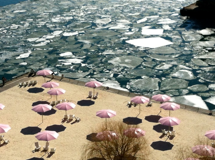 Sugar Beach, Toronto, April 1, 2015. Sandy beach with pink umbrellas in foreground, ice floes on the lake in background.