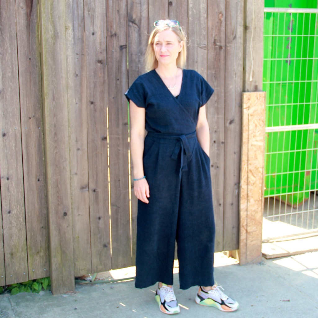 Frivolous at Last: Zadie Jumpsuit. Lori is standing in front of a wooden fence wearing a navy blue jumpsuit that wraps at the front and has a tie belt, and colourful sneakers.