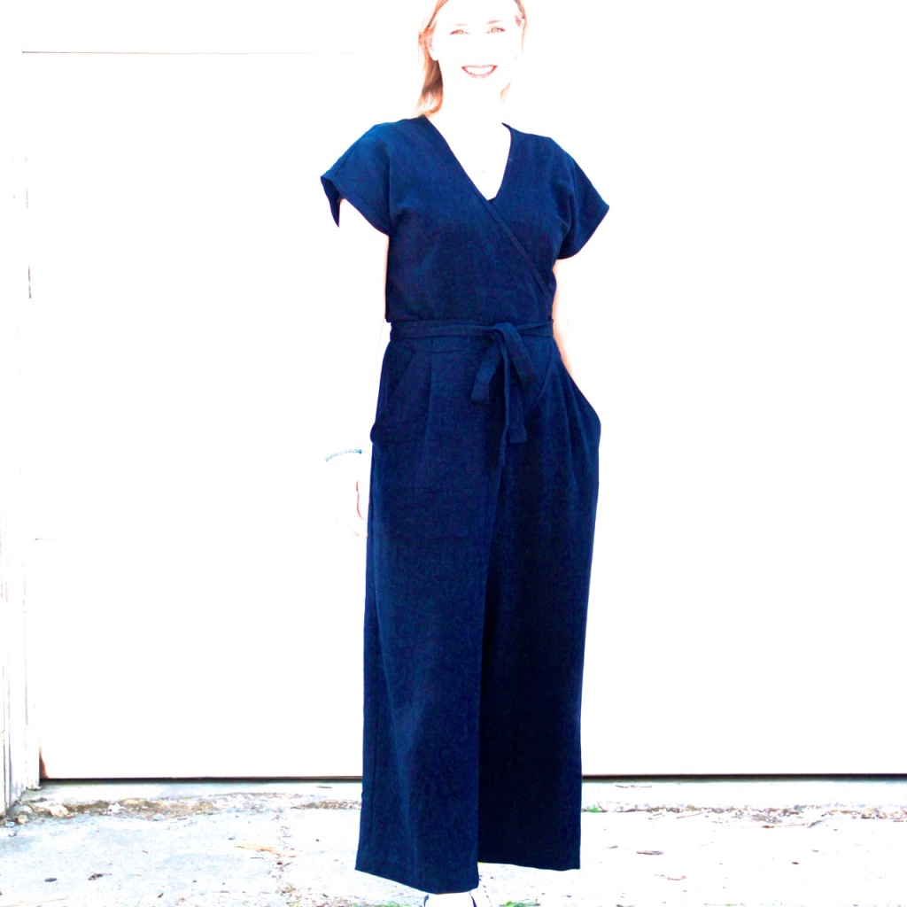 Lori stands smiling wearing a navy blue jumpsuit that wraps at the front and has a tie belt. The photo is completely over-exposed so you can barely see Lori but the blue jumpsuit is clearly visible.